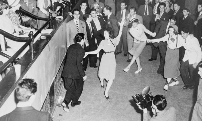 Back & White photo of men & women dancing west coast swing in a crowded dance floor and room