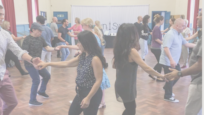 A west coast swing group of men and women dancing west coast swing dancers in a church hall with a dark parquet floor.